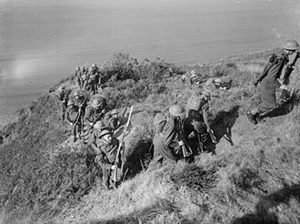 140th (4th London) Brigade - Men of the 2nd Battalion, London Irish Rifles advancing with fixed bayonets after climbing up the cliffs during training at Little Haven near Haverfordwest.