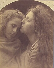 A woman's cheek rests on the forehead of a younger girl. Both appear calm and are draped in fabric from the neck down.