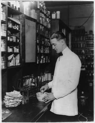 Compounding - Pharmacist compounding a medication using a mortar and pestle (c. 1923)