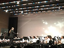Conductor leads band students onstage