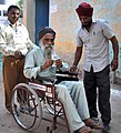 The physically handicapped voter displaying his identity card, at a polling booth during the 3rd Phase of General Elections-2014, in New Delhi on April 10, 2014.jpg