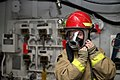 U.S. Navy Hull Maintenance Technician Fireman Ariel Peterson dons a firefighting helmet during a general quarters drill aboard the aircraft carrier USS George Washington (CVN 73) April 26, 2013, at Naval Base 130426-N-BX824-017.jpg