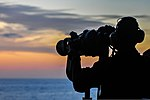 U.S. Navy Seaman Villard Vitalis, assigned to the amphibious assault ship USS Boxer (LHD 4), uses the ship's binoculars to search for surface targets while on watch in the Arabian Sea Oct. 23, 2013 131023-N-GM561-134.jpg