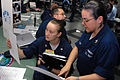 U.S. Navy Storekeeper 3rd Class Catrina Mahill learns about the intelligence specialist rating from Intelligence Specialist 1st Class Sonia Trotter at a career fair aboard aircraft carrier USS Ronald Reagan (CVN 090822-N-RJ456-114.jpg