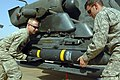 US Army 52453 CAMP TAJI, Iraq - Spc. Sean McConnell (left), of Columbus, Ohio, and Spc. Scott Shaver, of Austin, Texas, load a Hellfire missile onto the mounting bracket on an AH-64D Apache helicopter, here, Oct. 1.jpg