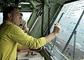 US Navy 030325-N-6610T-513 Cdr. Michael Zemesnik, Air Boss aboard USS Bataan (LHD 5) writes down departure times of aircraft on the window of Primary Flight Control.jpg