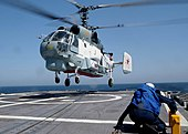 US Navy 030612-N-4374S-001 A blokbremsas kaj ĉenas skipon, parton de la flugferdekteamo sur la Egido-krozŝipo USS Vella Gulf (CG 72) restas en preta pozicio dum rusa Helix K-27-helikoptero alteriĝas sur ship.jpg