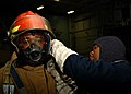 US Navy 050914-N-6495K-007 Personnelman 2nd Class Dewitt Washington, left, is assisted by Yeoman Seaman Zion Johnson, right, in donning his fire gear to participate in a General Quarters (GQ) drill.jpg