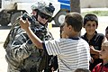US Navy 080806-N-0373Q-044 Local Iraqi children get a glimpse of themselves as U.S. Navy Mass Communication Specialist 2nd Class Angela Mclane shares her imagery with them near the Buhraz police station.jpg