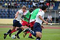 US Navy 080917-N-7526R-338 Lt. Craig Ruhs, a member of the Commander, Navy Region Europe soccer team, races past two defenders for the Gabonese Division 1 soccer team FC Missile during a match at Gabon's national stadium in Lib.jpg