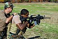 US Navy 081107-N-0411D-017 Senior Chief Mass Communication Specialist Andrew McKaskle guides Mass Communication Specialist 2nd Class Herbert Banks in a tactical shooting portion of firing range training.jpg