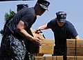 US Navy 100130-N-5244H-055 ailors assigned to the amphibious dock-landing ship USS Carter Hall (LSD 50) unload a truck bed of meals-ready-to-eat (MREs) at a Birey, Haiti school.jpg