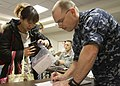 US Navy 110324-N-0640G-024 Senior Chief Personnel Specialist Matthew Winstel helps a woman with travel orders and other paperwork in the Forward Jo.jpg