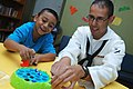 US Navy 111018-N-BX435-035 Logistics Specialist Seaman Almondo Marcus, assigned to Navy Operational Support Center El Paso, plays with a child at C.jpg