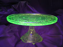 A glass place on a glass stand. The plate is glowing green while the stand is colorless.