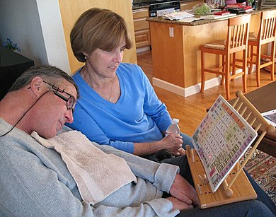 A man with ALS communicates with his wife by pointing to letters and words with a head mounted laser pointer.