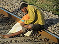 Waste Picker checking his wounds on the railway track.JPG