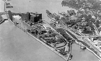 Welland Canal - Aerial photo of Port Dalhousie from the third canal era. 3rd canal lock at left, 2nd canal lock at right. Note 3rd canal towpath at upper left and Muir brothers' ship yard centre right.