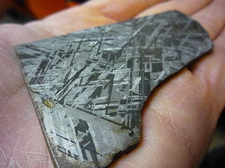 A polished and chemically etched piece of an iron meteorite, believed to be similar in composition to the Earth's metallic core, showing individual crystals of the iron-nickel alloy (Widmanstatten pattern). Widmanstatten hand.jpg