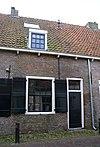 foto van Eenvoudig woonhuis in gele baksteen onder een gezamenlijk met de nrs 4,6 en 10 dwars, met pannen belegd zadeldak
