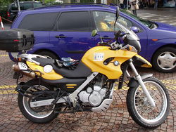 Yellow BMW F650GS fitted with optional top box and parked next to a blue car