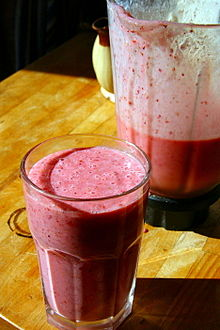 berry smoothie in a glass with blender