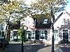 foto van Huis met rechte kroonlijst, in midden topgeveltje, dak met riet gedekt