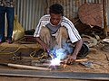 A solder working on Andranofasika market, January 2010, Madagascar (4463937898).jpg