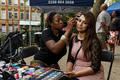 African Street Style Festival 2016 - A woman poses for the camera while her face is painted by an artist.png