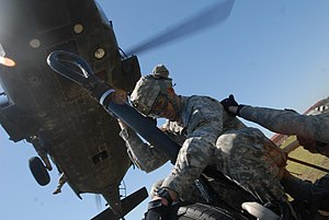 Air Assault Badge - Soldier prepares to slingload an M119A2 howitzer to a UH-60 Black Hawk