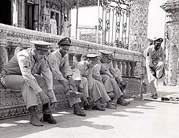 A line of six black American soldiers in service uniform (non-combat) sitting or standing beside the railing at the entrance of a temple. All are taking off their shoes prior to entering the temple.