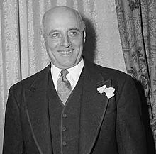 A smiling, bald man in a suit