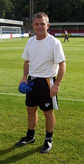 A blond-haired man in his 40s, wearing a white T-shirt and black shorts, stands near the edge of a football pitch.