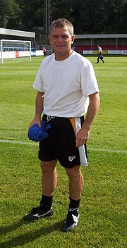 A middle-aged man, wearing a white T-shirt and black shorts, standing on a grass field.