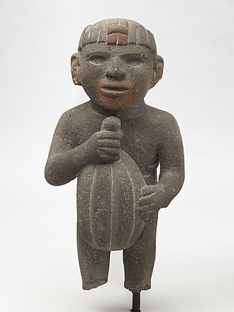 Chocolate - Aztec. Man Carrying a Cacao Pod, 1440–1521. Volcanic stone, traces of red pigment. Brooklyn Museum