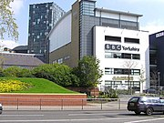 "A quirky modern five-storey building with a large sign saying ""BBC Yorkshire"" in black above the second-floor windows on the white-fronted façade of the lower four floors can be seen on the far side of a dual-carriageway road with a barrier along the central reservation. At right-angles to the right of the building is a tall blue slab with the letters ""BBC"" in white at the top. The left side of the building is mostly brick-red with a few windows, but above it is a light blue windowless section. The roof above this and the grey fifth floor of the frontage curves gently down to the rear. A lone car is driving from left to right along the road; between it and the building, temporary boards have been erected in front of a building to the left. In the top left-hand corner of the picture, part of a tall many-windowed building can be seen."