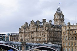 Un grand bâtiment rectangulaire de pierre grise comportant une multitude de fenêtres et une grande tour carrée en arrière plan comportant une horloge. Un pont est visible au premier plan et traverse un espace entre ce bâtiment est un autre de même style