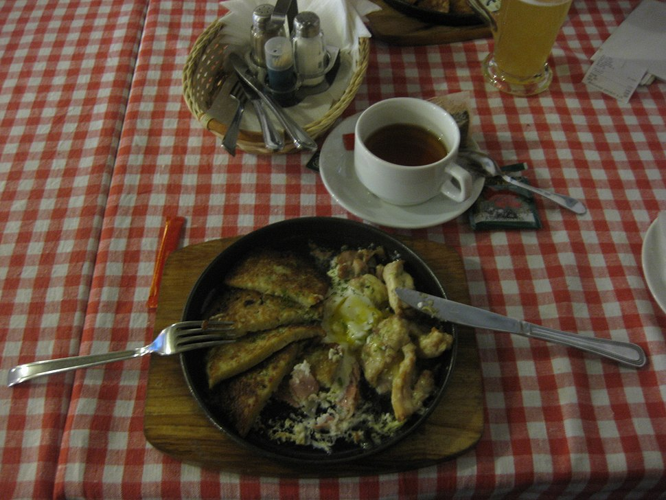"""Belorussian national potato meal """"draniki"""" and a cup of drink."""