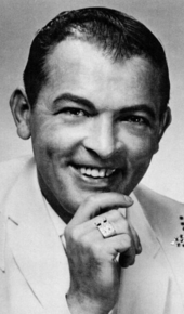 A dark-haired man smiling wearing a white jacket, smiling broadly and holding one hand to his chin