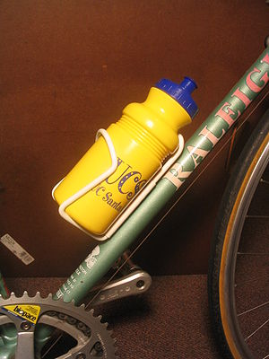Bottle cage - White bottle cage holding water bottle, attached to down tube