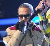 A picture of a man wearing glasses while holding a microphone in their hands wearing a thick jacket and gloves