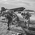 British paratroops fitting their parachute harnesses before entering a Dakota during a large-scale airborne forces exercise, 22 April 1944. H37706.jpg