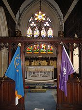 alter of a neo-Gothic church, showing colourful stained glass windows, with two flags posted in the foreground
