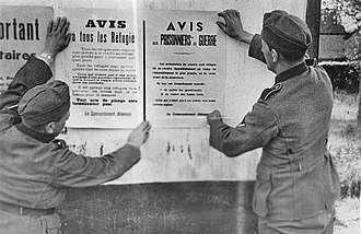 Internment camps in France - German soldiers posting notices for refugees and prisoners of war in France, May 1940