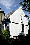 foto van Houten huis op bakstenen onderbouw, tegen de helling opgetrokken