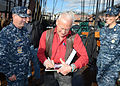 Buzz Aldrin autographs a photo. (10405533815).jpg