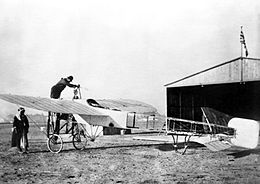 Single-engined monoplane on airfield in front of hangar with Union Jack on flagpole