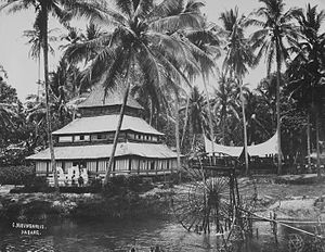 Payakumbuh - Pajakoemboeh scene with water wheel, children swimming, a mosque and a Minangkabau town hall in the background