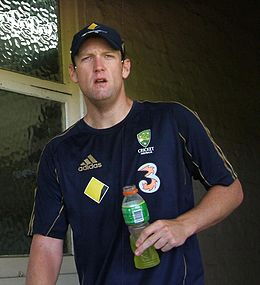 A man is peering in front of him, holding a drinks bottle with a yellow liquid in. He is wearing a dark blue t-shirt with gold piping, and four logos on it. He is also wearing a baseball cap of the same colours.