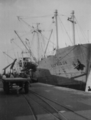 Cargo ship is loaded at the port of Dakar 1956.png